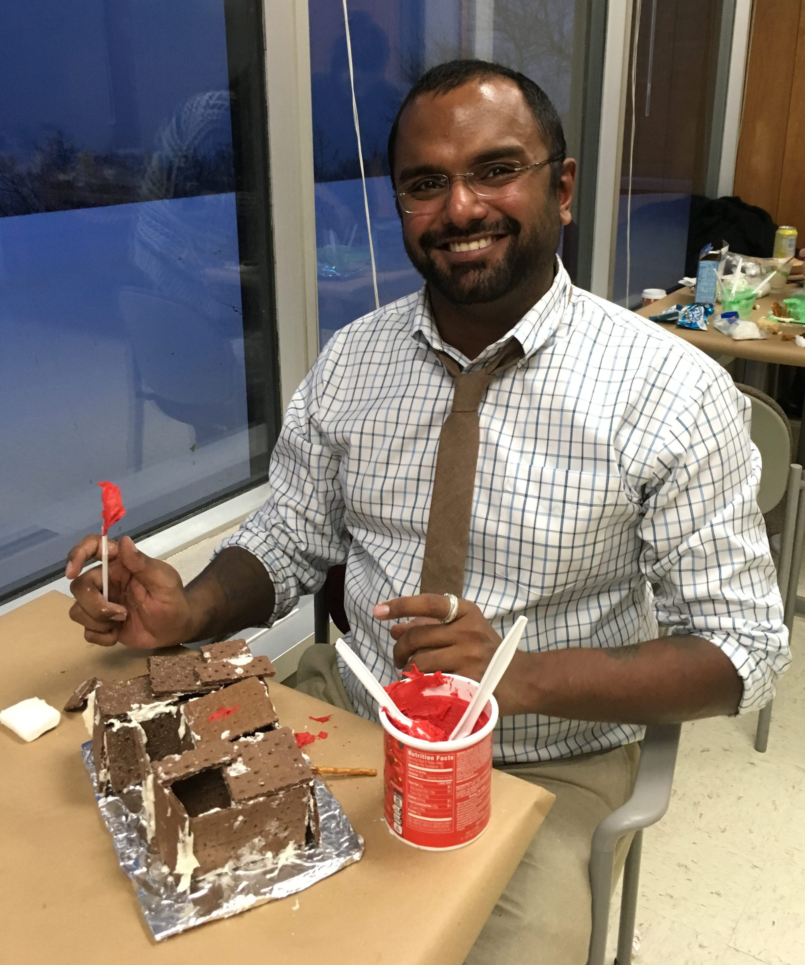 Photograph of Akshay Sarathi building a gingerbread house