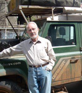 Photograph of Professor Herbert Lewis standing by truck in the field.