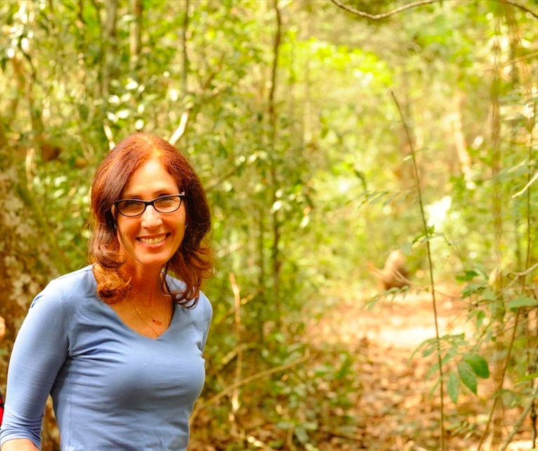 photo-Karen Strier in forest with muriqui in background