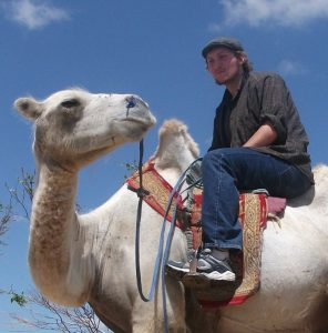 Photo of Kip Hutchins riding a camel