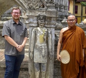 Photo of Mathew Trew with statue and Buddhist Monk